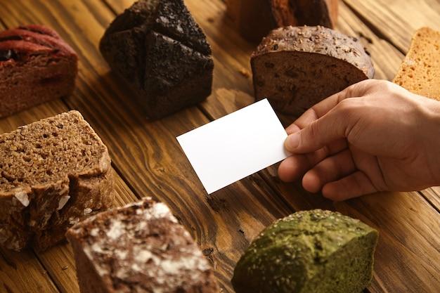 Biglietto da visita in bianco del panettiere artigianale professionista presentato in mano al centro di molti campioni di pane esotico al forno alternativi misti sopra il tavolo rustico in legno