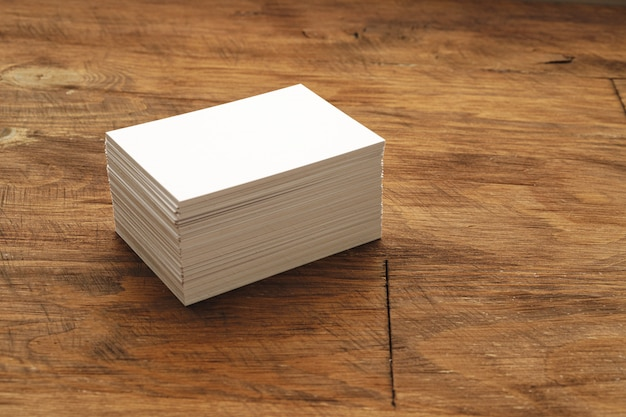 Blank business card stacks on rough wooden table