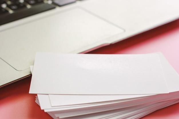 Пустые визитки и компьютер ноутбук на розовом фоне цвета