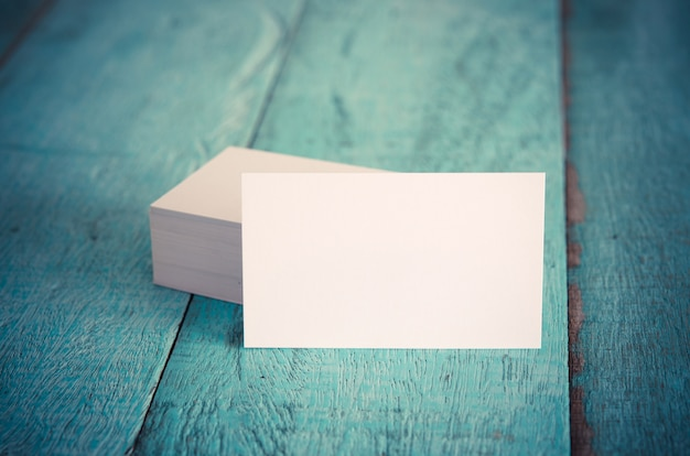 Blank business cards on blue wooden table.