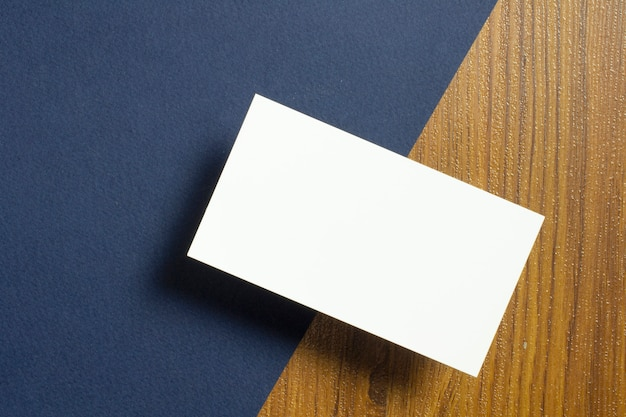 それぞれの半分の空白の名刺が青い織り目加工の紙と木製の机の上に横たわる