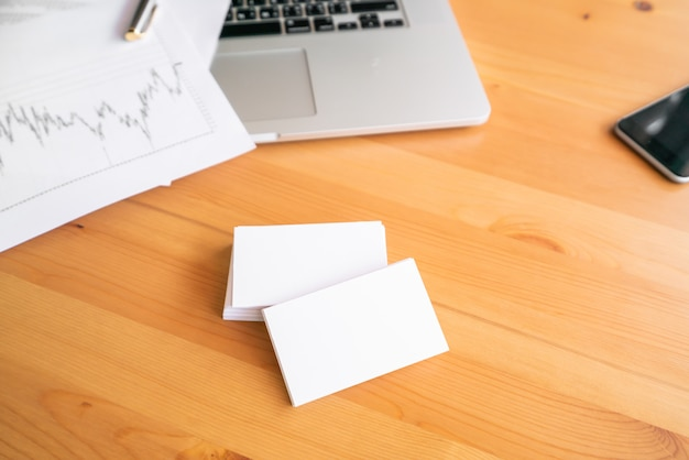 Blank business cards and laptop on wooden surface