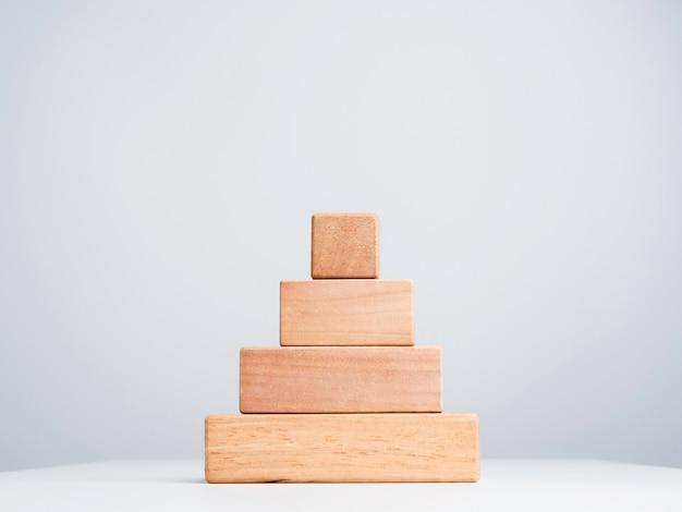 Шаги пустой бизнес-диаграммы, сделанные стеком деревянных кубических блоков в форме пирамиды, изолированной на белом фоне, экологически чистом и минималистском стиле.