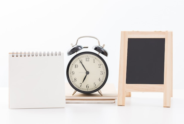 Blank calendar and blackboard and clock time at five minute to seven o'clock on white