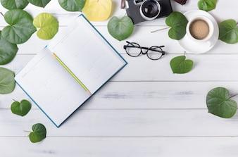ハート型の緑の葉とコーヒーを持つ空のカレンダー