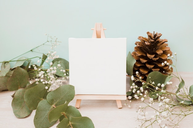 Blank canvas on miniature easel with leaves; pinecone and baby's-breath flowers on wooden desk against green background
