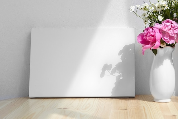 Blank canvas and vase with pink flowers on table white wall