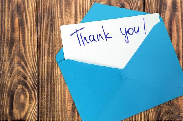 Пустая карточка и конверт с благодарностью на фоне
