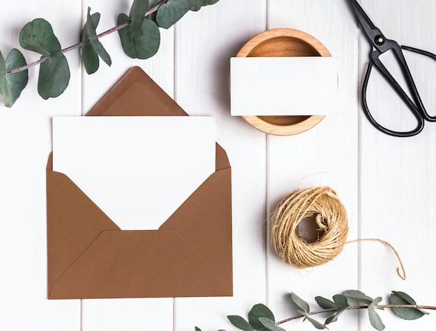 유칼립투스 나뭇가지가 있는 나무 탁자에 있는 봉투에 빈 카드와 종이