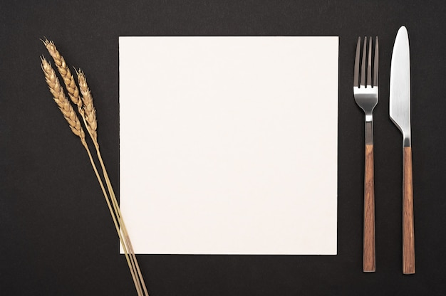 Blank card and cutlery on black table top view white recipe paper page