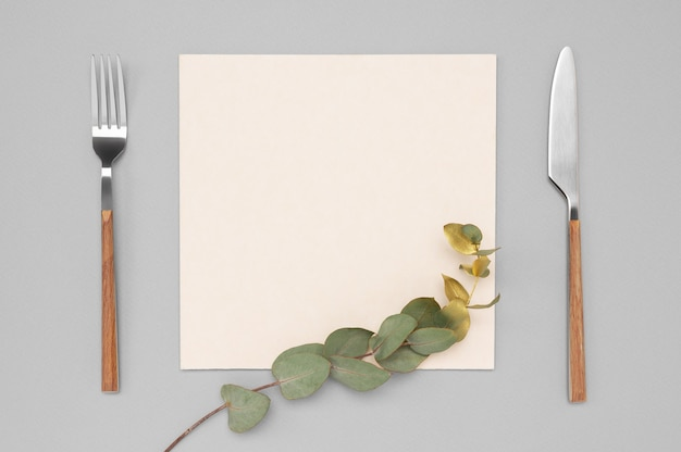 Blank card and cutlery. knife and fork with white paper for menu or recipe text and gold eucalyptus branch.