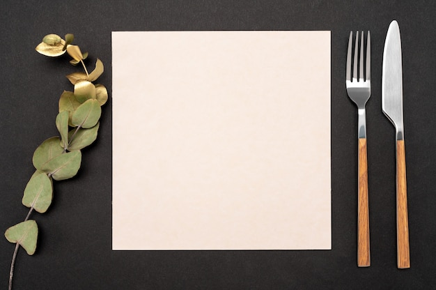 Blank card and cutlery. knife and fork with white paper for menu or recipe text and gold eucalyptus branch