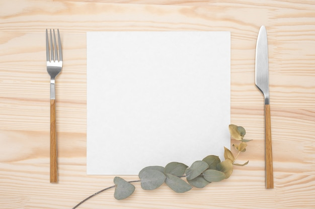 Blank card and cutlery on rustic wooden table. knife and fork with white paper