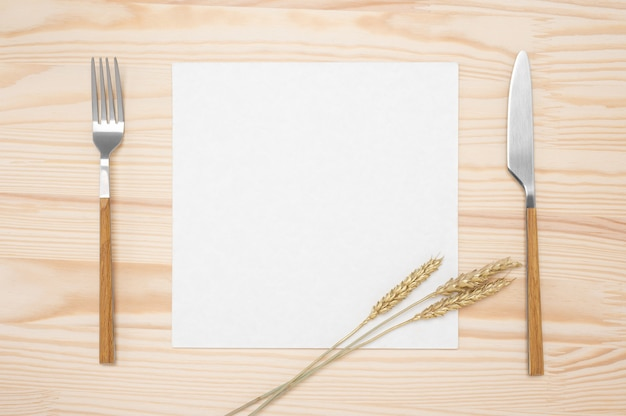 Blank card and cutlery on wooden table. top view white recipe paper page, card and cutlery