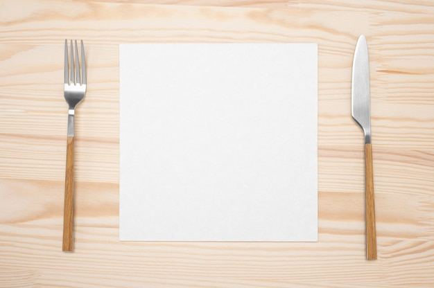 Blank card and cutlery on wooden table. top view white recipe paper page
