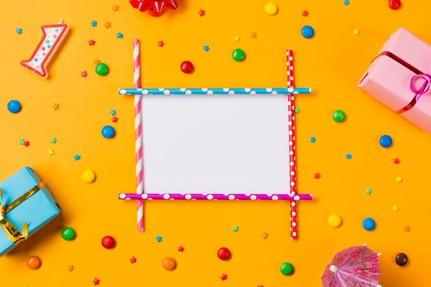 Blank card decorated with gift boxes and colorful confectioneries on yellow background