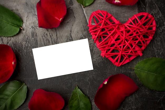 バラの花と暗い背景に赤いハートの間で署名のための空白のカード。バレンタインデーや結婚式。上からの眺め