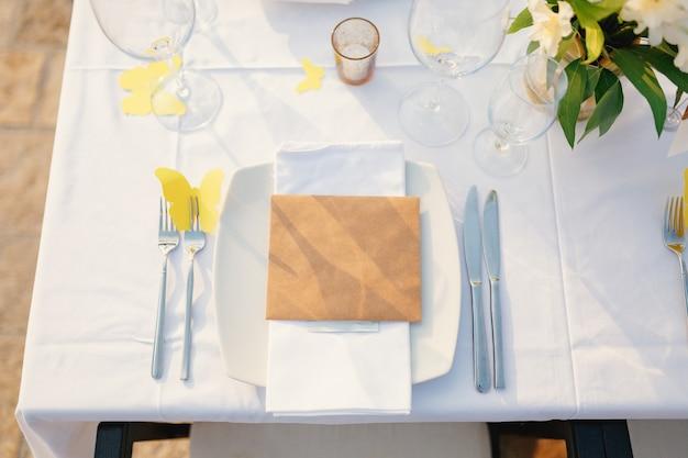 空白のカードは、夕食のために美しく提供されたテーブルの皿の上にあります