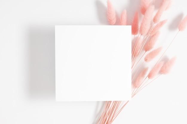 흰색 배경에 토끼 토끼 꼬리 잔디 꽃다발 빈 카드 또는 메모