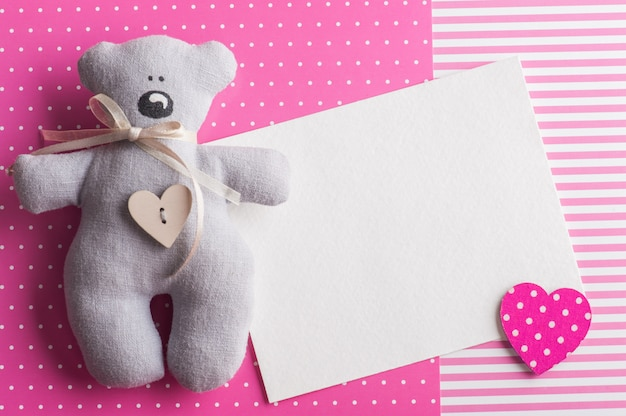 Blank card on pink background with teddy bear