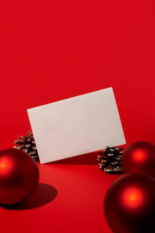 Blank card and red christmas balls and pine cones on red table
