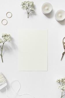Blank card surrounded with gypsophila; wedding rings; string and scissor on white background