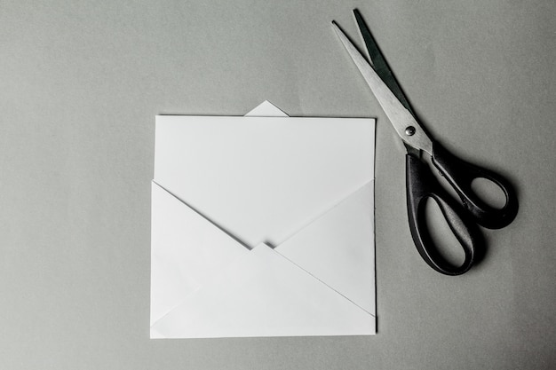 Blank card in white envelope and scissors
