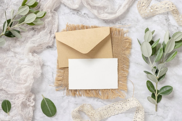 Blank card with envelope laying on a marble table decorated with eucalyptus branches and ribbons