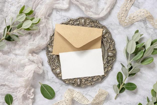 Blank card with envelope on vintage plate on marble with eucalyptus branches and vintage ribbons around. card mockup