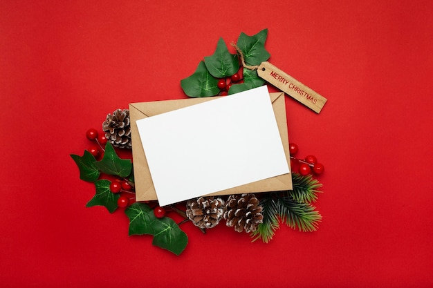 Blank card with mistletoe and pine cones on red table