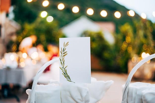 장식 된 빈 카드 테이블에 흰 고리 버들 세공 바구니에 압 연된 수건에 서