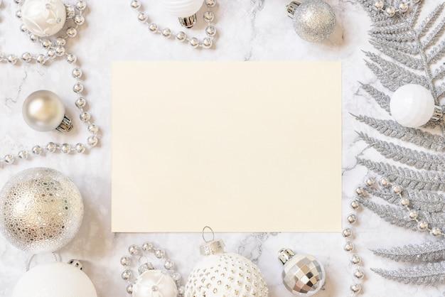 Заглушка с серебряными и белыми елочными украшениями на белом мраморном столе. макет рождественской или новогодней открытки, копией пространства. концепция зимнего отдыха