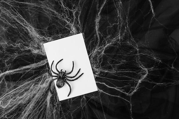 黒の背景の上に蜘蛛の巣と空白のカード。ハロウィーンのコンセプト。