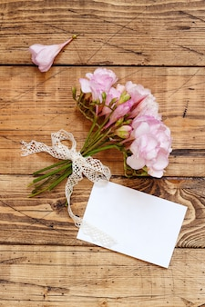 Blank card on a wooden table between pink flowers close up