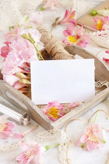 Blank card on a wooden tray between pink flowers close up