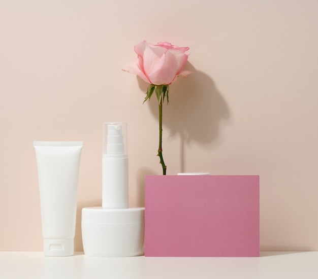 Blank cardboard business card and a set of jars, tubes and plastic bottles on a beige background. cosmetic branding, promotion and advertising