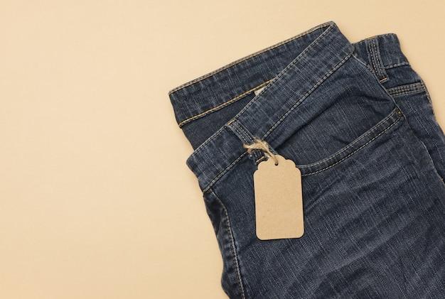 Пустая картонная бирка прямоугольной формы, привязанная к синим джинсам. вид сверху, копировать пространство