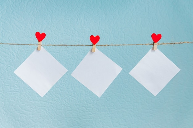 Blank cards on pins with red hearts. mockup for text and blue background for valentines day greetings