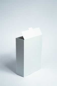 Blank carton food package, vertical view on white surface