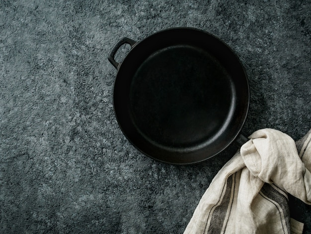 Blank cast iron frying pan on dark grey concrete background