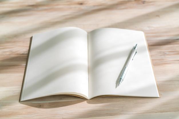 빈 카탈로그, 잡지, 책 나무 배경에 펜으로 조롱.