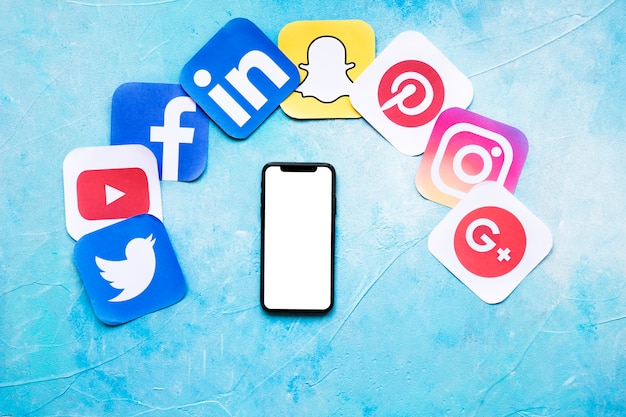 Blank cellphone with various social networking paper icons on blue backdrop