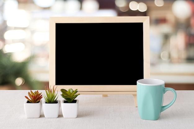 Bokeh 배경 흐림 레스토랑 위에 빈 칠판과 녹색 커피 컵 서