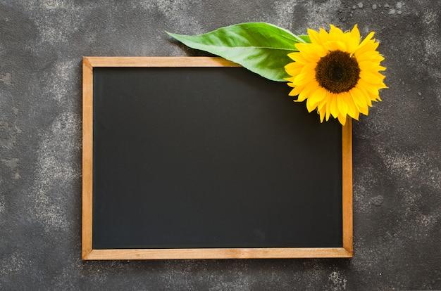 Blank chalkboard on dark stone with sunflower