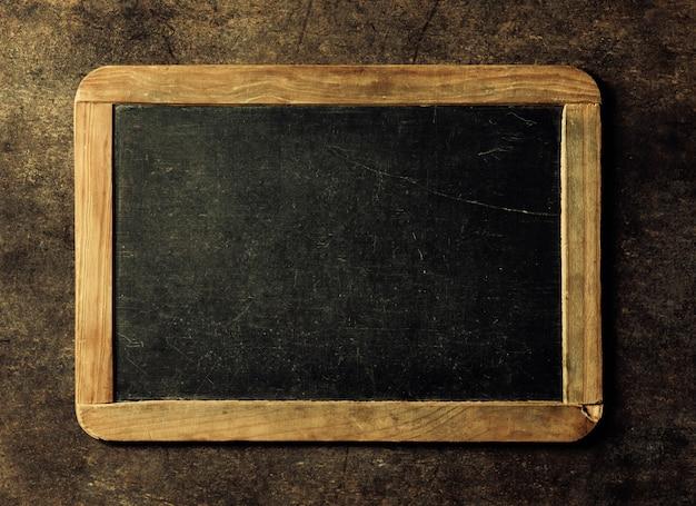 あなたのテキストの空の黒板。木製のテーブルの上から見る