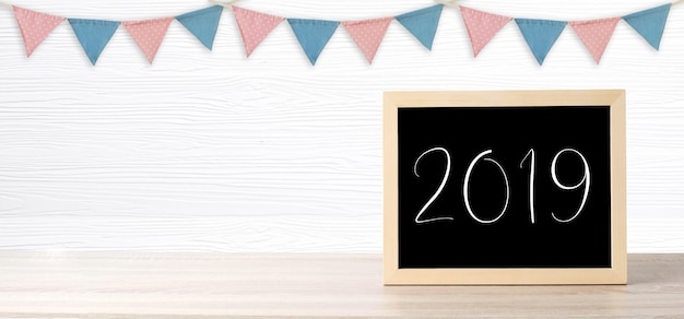 Blank chalkboard standing over colorful party flags hanging on white wood background