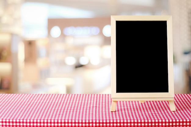 赤と白のテーブルクロスに立っている空白の黒板