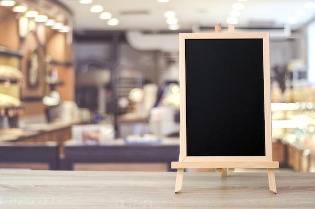 ボケの背景とぼかしカフェの上にテーブルに立って空白の黒板