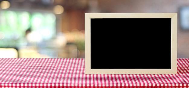 ボークスの背景とぼかし店の上にテーブルに立っている空白の黒板