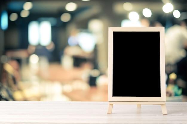 ぼかしレストランの上に木製のテーブルに立っている空白の黒板